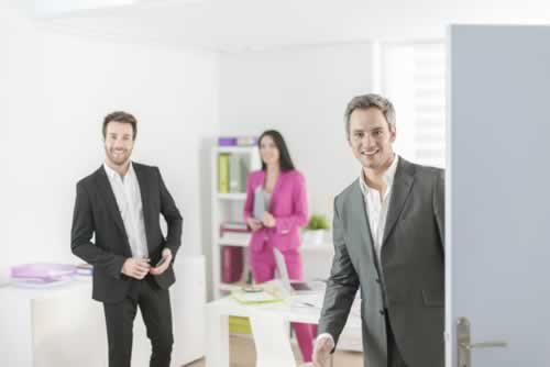 Image of an open office door with three people inside